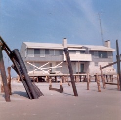 """""""Ninth and beach. This house was built the previous year by a building contractor. There were large dunes in his front yard, so he had them plowed down to improve the view. He also build on the cheap, on a slab, with pilings around the perimeter only. When the waves undermined the slab, the whole first floor fell out with all the furniture. We walked under the house and looked up to the second floor."""" - Jim Thatcher"""